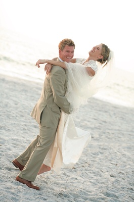 Groom in khaki suit picks up bride in lace wedding dress on beach