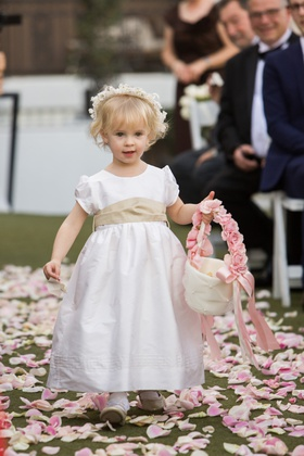 young flower girl with white dress, tan sash, flower crown, basket with pink handle