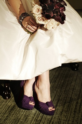 Bride in a pale pink gown and purple Louboutin heels holds a bouquet