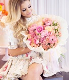 Bride to be in short flower print dress with curled hair pretty makeup large bouquet