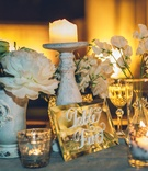 table with glass vases, candle stands and votives and white flowers