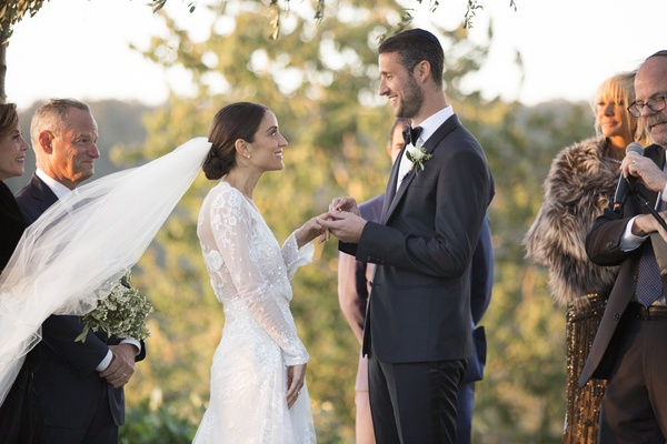 bride's veil blowing in the wind as groom puts ring on her finger during ceremony