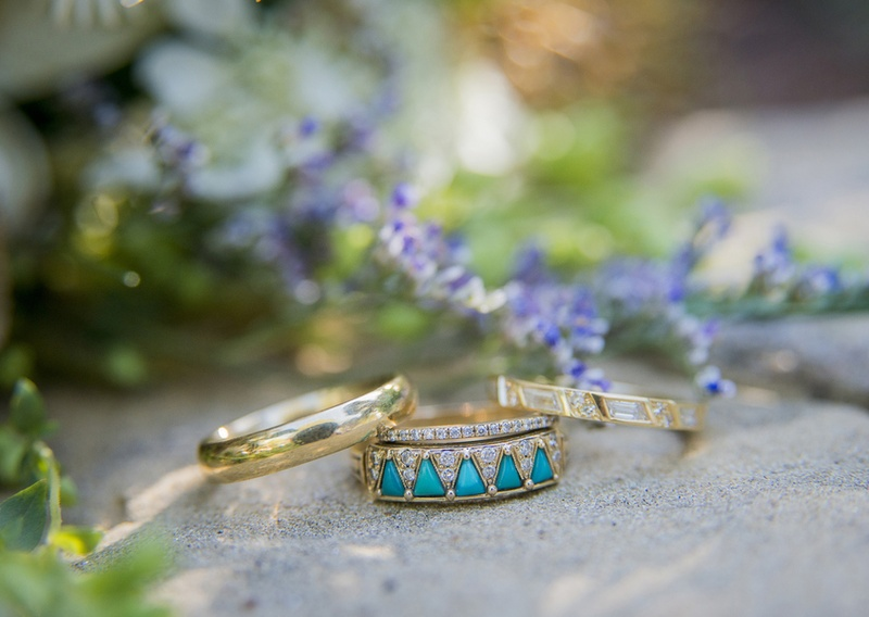 unique gold ring bands with small diamonds and turquoise gems on a rock outdoors