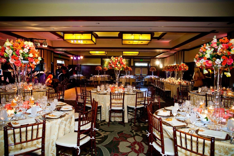 Brightly colored floral centerpieces on gold linens