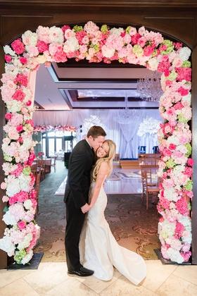 bride in romona keveza, groom in suit, newlyweds pose in pink floral frame of hydrangeas
