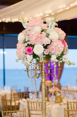 Pink and white flowers atop gilt candelabra