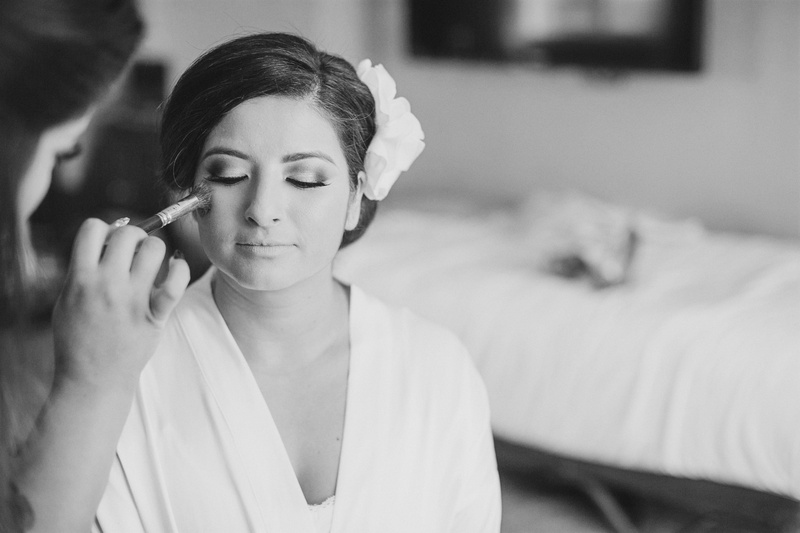 Black and white photo of makeup artist applying blush to bride