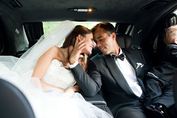 Newlyweds with son kiss in car