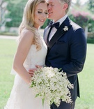 Wedding portrait bride with long blonde hair curled white wedding dress lily of the valley bouquet