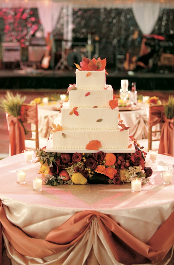 Fall leaf decorated white wedding cake on harvest fruit stand