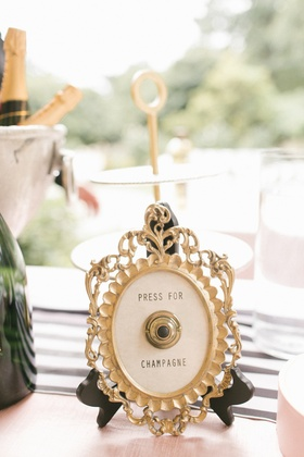 framed button to press for champagne at wedding bar