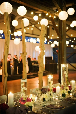 Reception table decorated with tall vases with submerged orchids and floating candles and flowers