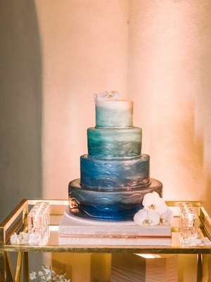 Four layer wedding cake painted with dark blue fading to light sea foam green and white fondant