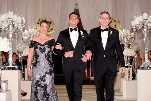 Chad Carroll with mother of the groom and father of the groom walking down aisle