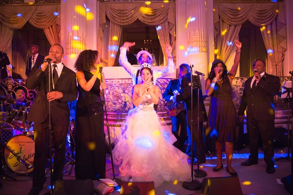 bride and groom on stage with wedding band at reception pink and purple lighting