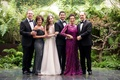 Bride with mother in off shoulder grey gown and groom mother in long sleeve fuchsia dress tuxedos