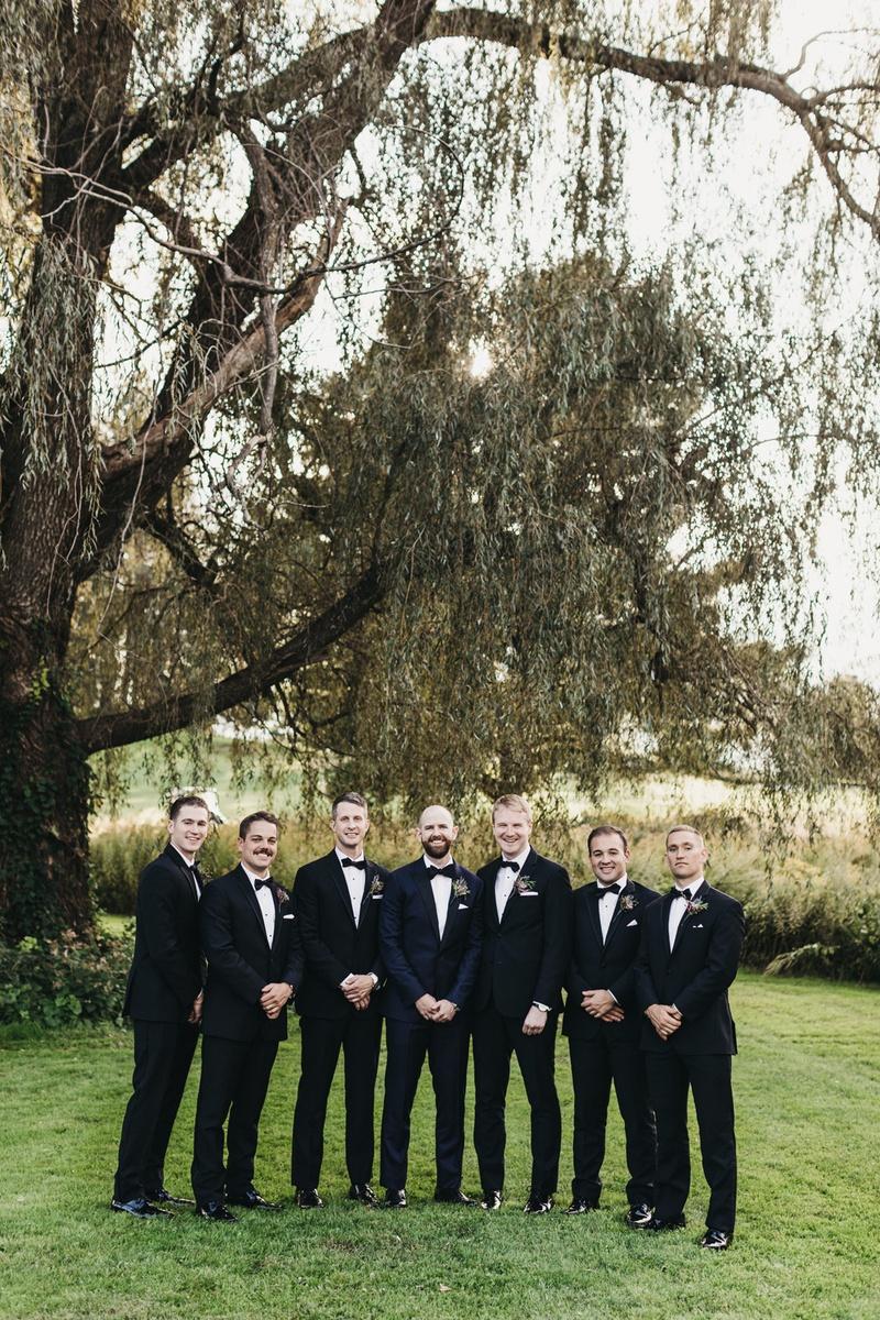 groom in midnight blue tuxedo in center of group of 6 groomsmen in black tuxes