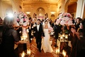 Bride in fit-n-flare gown and groom walk up ballroom aisle
