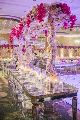Mirror table with Lucite chairs and metal scaffolding wedding centerpiece with flowers and glass orb