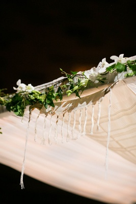 Tallit at Jewish wedding ceremony on top of chuppah with green garland and white flowers