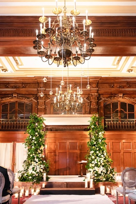 wedding ceremony wood paneled ballroom greenery white flower chuppah candles oval back wood chairs