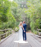wedding portrait on bridge bride in sleeveless wedding dress groom in blue suit bridge santa barbara