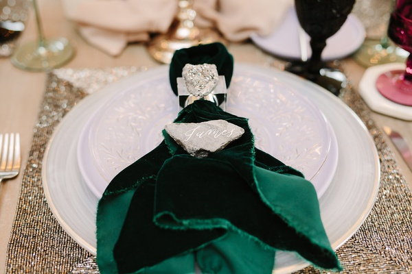 rock used as place card on top of forest green velvet napkin
