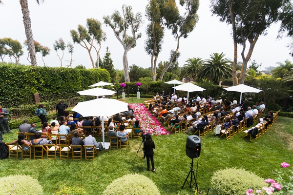 overview of ceremony on lawn with pink petal aisle