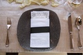 Textured grey charger plate beaded with napkin, menu, belly band and champagne linens flower petals