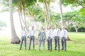 groom in grey suit, groomsmen in grey slacks and suspenders