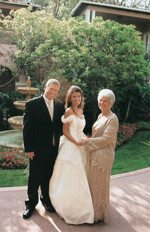 bride wearing off the shoulder dress with parents
