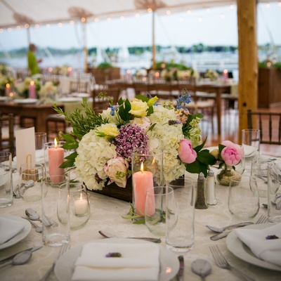 centerpieces with pink peonies, purple, white, blue, and yellow flowers, peach candles in hurricanes
