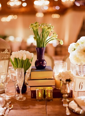 Small floral arrangements atop stack of books