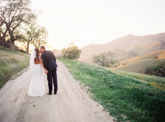 Bride in keyhole back wedding dress kisses groom on ranch