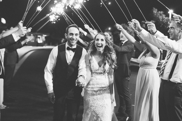 black and white photo of groom in vest and bride in lace gown during sparkler exit