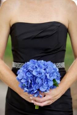 Bridesmaid in black dress holding blue hydrangeas