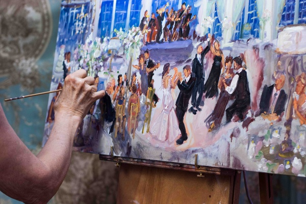 Woman painting picture of bride and groom at reception