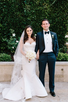 Bride in strapless wedding dress oscar de la renta mermaid groom with bow tie and tuxedo bouquet