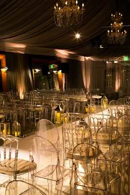 dimly lit ceremony space with white aisle runner ghost chairs and small votives lining aisle