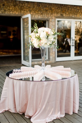floral arrangement on mirrored table, escort card display fanned out on mirrored table with blush li