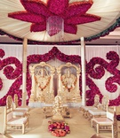 south indian wedding ceremony altar with fuchsia blossoms arranged in scroll on ceiling