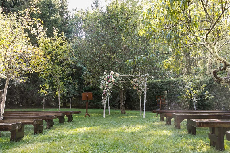 wedding ceremony wood pews benches birch branch arch with greenery pink flowers