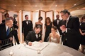 a jewish bride and groom signing the ketubah with friends and family around before ceremony