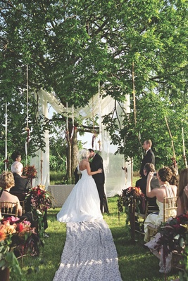 Bride and groom kissing at alfresco wedding