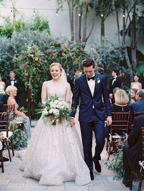 bride in sparkle lazaro wedding dress high neck updo green and white bouquet groom navy tuxedo