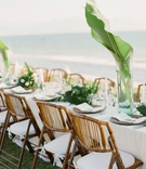 Wedding reception overlooking beach and ocean white table wood vintage looking chair green leaves
