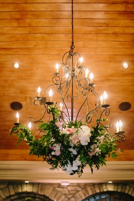 wrought iron chandelier with white orchids, pink peonies, and greenery