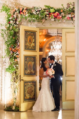 Bride and groom under floral door at The Plaza Hotel