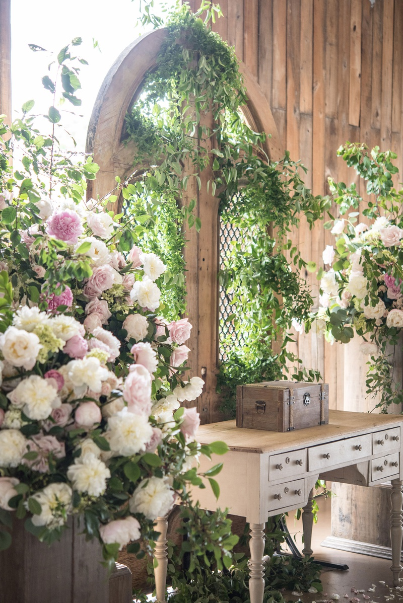 barn wedding, greenery on gate as wedding backdrop, table, pink and white floral arrangements