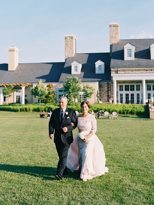 wedding ceremony lawn green grass countryside resort mother of bride in pink dress with father
